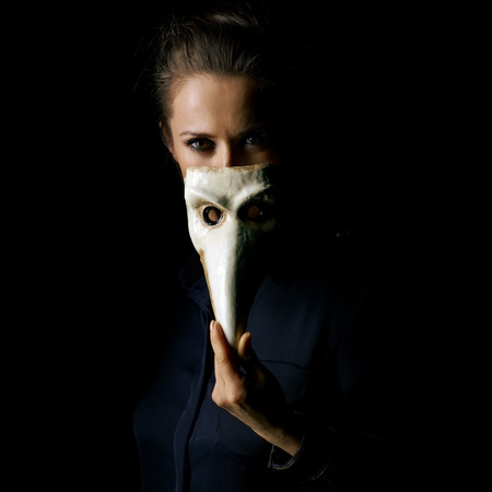 Сoming out into the light. Portrait of woman in the dark dress isolated on black hiding behind Venetian mask