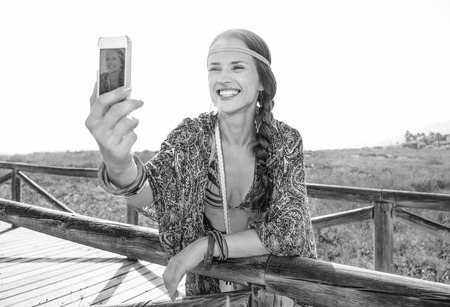 Bohemian vibe vacation. happy fashion boho girl in cape outdoors in the summer evening with smartphone taking selfie