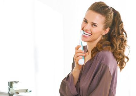 バスルームで歯を磨いて幸せな若い女 写真素材