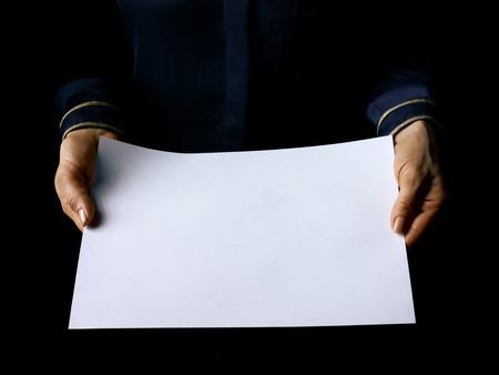 Black Mania. mani femminili isolate su nero mostrando foglio di carta bianca