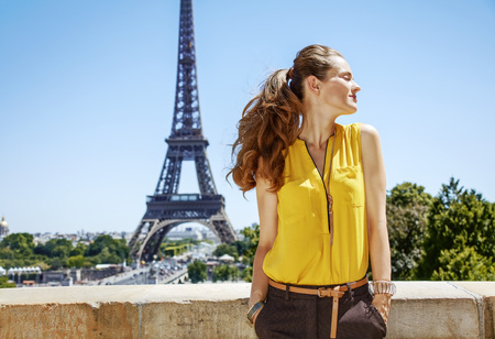 Having fun time near the world famous landmark in Paris. relaxed young woman in bright blouse against Eiffel tower