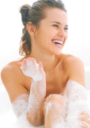 욕조에 거품을 가지고 노는 웃는 젊은 여자