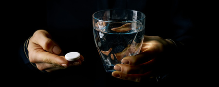 Black Mania. female hands isolated on black showing pill and glass of water
