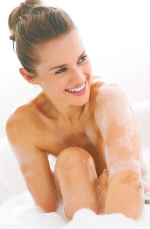 Smiling young woman sitting in bathtub Stock Photo