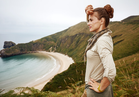 Into the wild in Spain. Portrait of adventure woman hiker looking into the distance in front of ocean view landscape 版權商用圖片