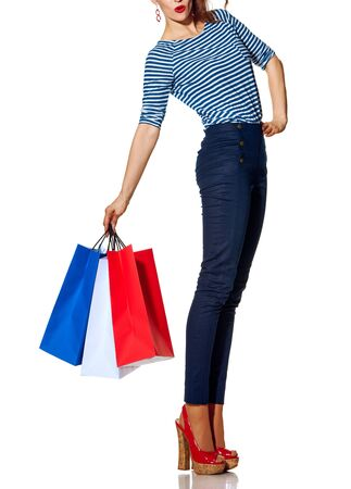 Boodschappen doen. De Franse manier. Close-up op vrolijke trendy vrouw met boodschappentassen van de kleuren van de Franse vlag geïsoleerd op een witte achtergrond