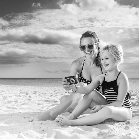 Sun kissed beauty. happy young mother and daughter in beachwear on the seacoast viewing photos on camera