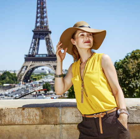 Having fun time near the world famous landmark in Paris. relaxed young woman in bright blouse looking into the distance against Eiffel tower 版權商用圖片 - 83845645