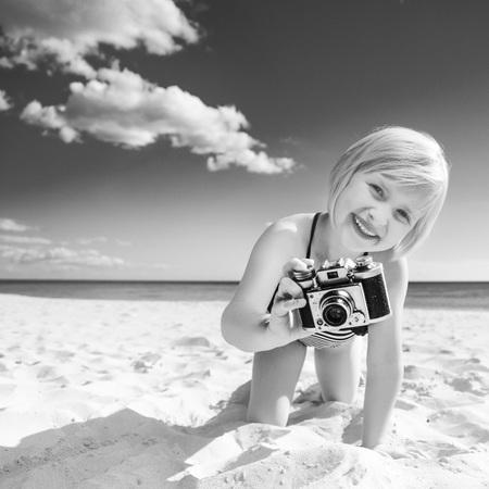 Sun kissed beauty. happy blond girl in beachwear on the seashore with digital camera taking photo