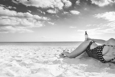Sun kissed beauty. Closeup on active woman in swimwear on the seashore with sun cream