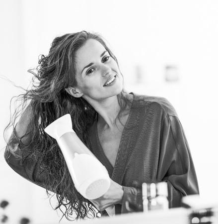 modern bathroom: Happy young woman blow drying hair in bathroom