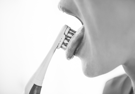 Closeup on young woman cleaning tongue using toothbrush