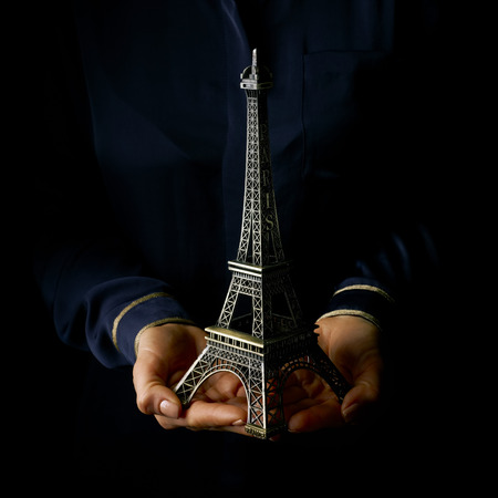 Black Mania. female hands isolated on black background showing eiffel tower