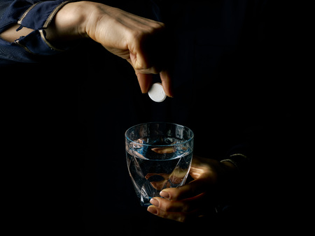 Black Mania. female hands isolated on black background showing effervescent tablet and glass of water