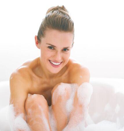 Portrait of happy young woman in bathtub
