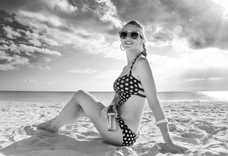 Sun kissed beauty. happy fit woman in swimsuit on the beach with SPF