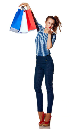 Shopping. The French way. Full length portrait of smiling trendy woman with shopping bags of the colours of the French flag isolated on white blowing air kiss Stock Photo