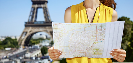 Having fun time near the world famous landmark in Paris. Closeup on happy young woman in bright blouse with map in Paris, France Stock Photo