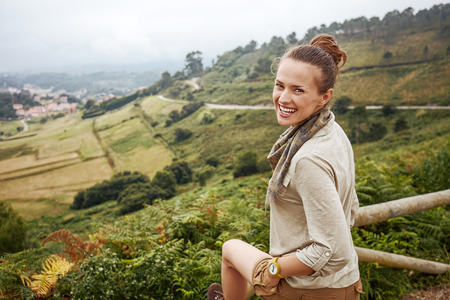 Into the wild in Spain. Portrait of smiling healthy woman hiker in front of beautiful landscape view