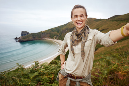 Into the wild in Spain. smiling adventure woman hiker taking selfie in front of ocean view landscape