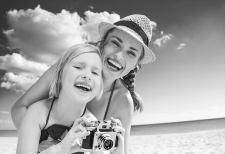 Sun kissed beauty. Portrait of happy young mother and child in swimsuit on the seashore with retro photo camera