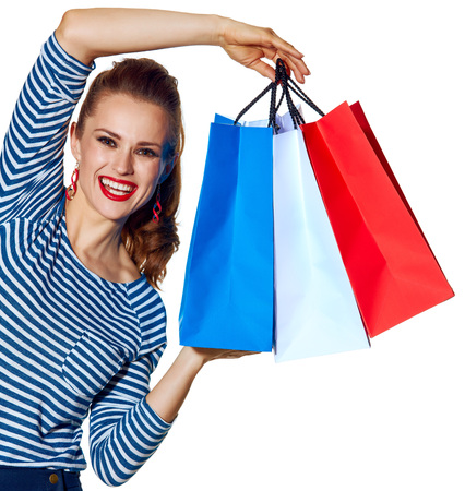 Shopping. The French way. Portrait of happy young fashion-monger showing shopping bags of the colours of the French flag isolated on white background
