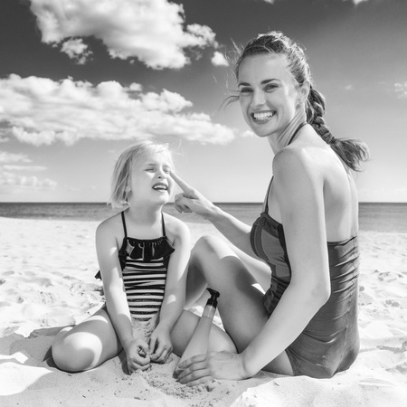 Sun kissed beauty. happy young mother and daughter in swimsuit on the beach applying sun block