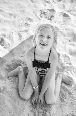 Sun kissed beauty. Portrait of smiling blond girl in swimwear sitting on the beach