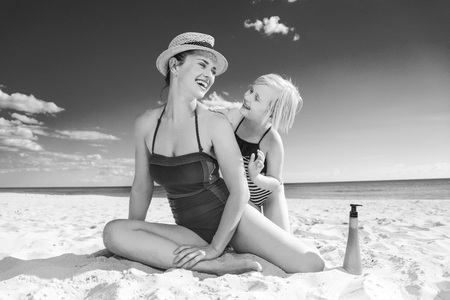 Sun kissed beauty. smiling young mother and child in beachwear on the seashore applying SPF Foto de archivo - 99980894