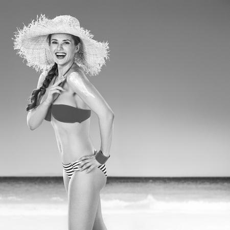 Perfect summer. happy healthy woman on the seashore applying sun screen