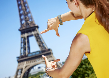 Having fun time near the world famous landmark in Paris. Seen from behind young woman in bright blouse framing with hands in Paris, France Stock Photo