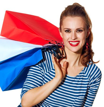 Shopping. De Franse manier. Portret van gelukkige stijlvolle vrouw met boodschappentassen van de kleuren van de Franse vlag geïsoleerd op wit