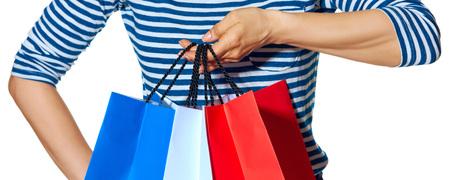 Shopping. De Franse manier. Close-up op stijlvolle mode-monger met boodschappentassen van de kleuren van de Franse vlag op een witte achtergrond