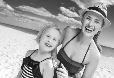 prophylaxis: Sun kissed beauty. happy healthy mother and child in swimwear on the seashore applying suntan lotion