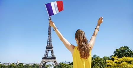 파리에서 세계 유명한 랜드 마크 근처 재미 시간을 보내고. 뒤에서 볼 에펠 타워 앞에서 밝은 블라우스 상승 플래그에 젊은 여자