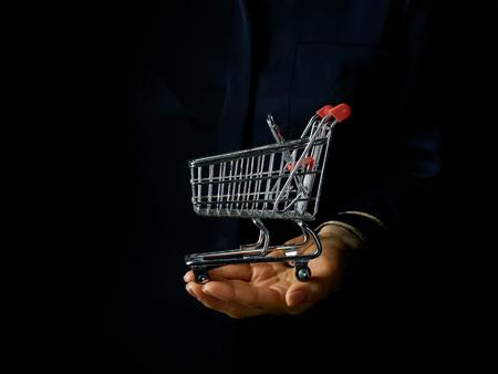 Black Mania. female hand isolated on black background showing mall shopping cart