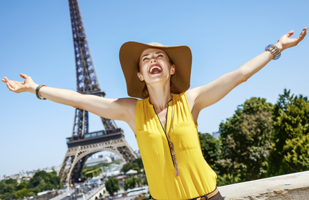 Having fun time near the world famous landmark in Paris. Portrait of smiling young woman in bright blouse rejoicing in the front of Eiffel tower Stock Photo