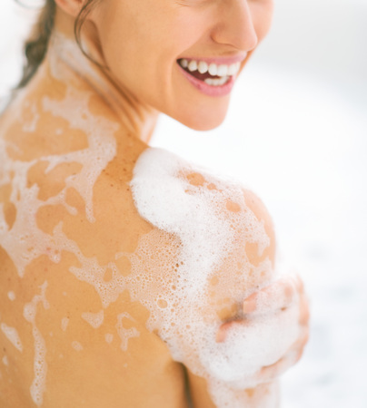 Closeup on happy young woman washing in bathtub Stock Photo