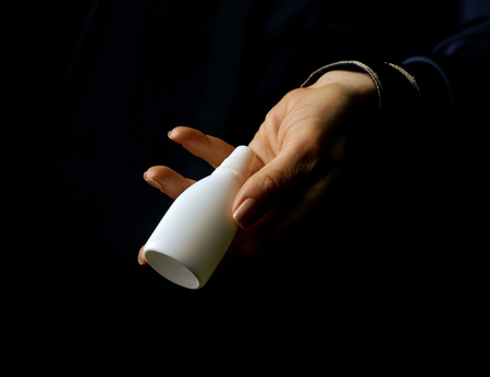 Black Mania. woman hand isolated on black showing bottle of medical drops