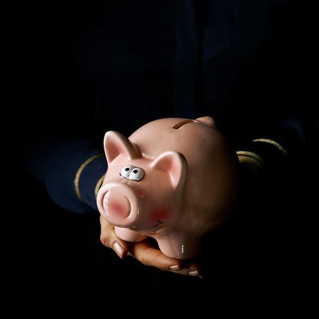 블랙 매니아. 여자 손을 돼지 저금통을 게재하는 검은 배경에 고립