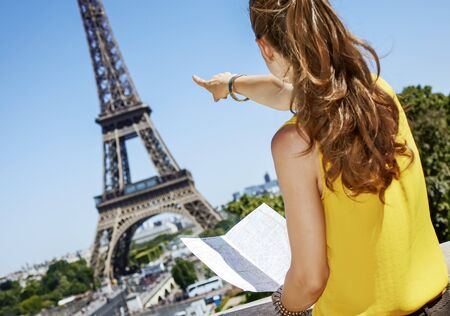 Having fun time near the world famous landmark in Paris. Seen from behind young woman in bright blouse holding map and pointing on Eiffel tower Stock Photo