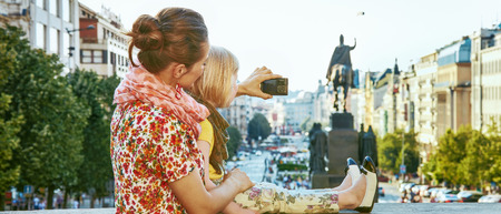 The spirit of old Europe in Prague. Seen from behind modern mother and child tourists in Prague, Czech Republic with digital camera taking photo