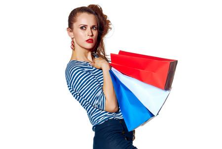 Shopping. De Franse manier. Full length Portret van trendy vrouw met boodschappentassen van de kleuren van de Franse vlag op een witte achtergrond opzij kijken