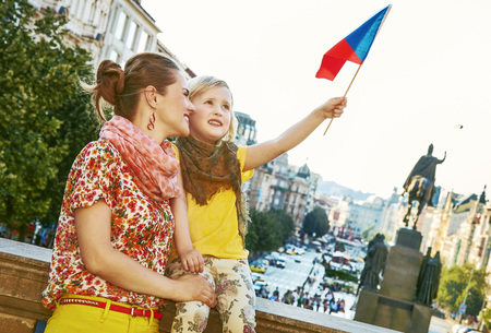 The spirit of old Europe in Prague. happy modern mother and daughter tourists on Vaclavske namesti in Prague, Czech Republic rising flag Standard-Bild - 99980899