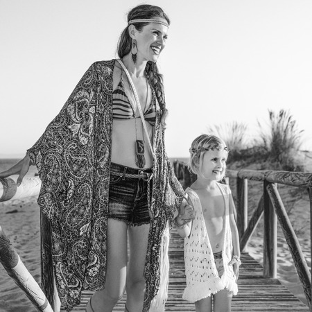Bohemian vibe vacation. Full length portrait of happy hippie mother and child outdoors in the summer evening looking into the distance Banco de Imagens
