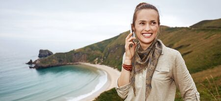 Into the wild in Spain. Portrait of smiling healthy woman hiker speaking on a cell phone in front of ocean view landscape Stock Photo