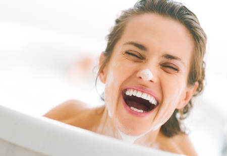 Portrait of smiling young woman with foam on face looking out from bathtub