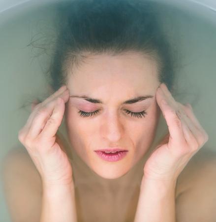 modern bathroom: Portrait of stressed young woman in bathtub Stock Photo