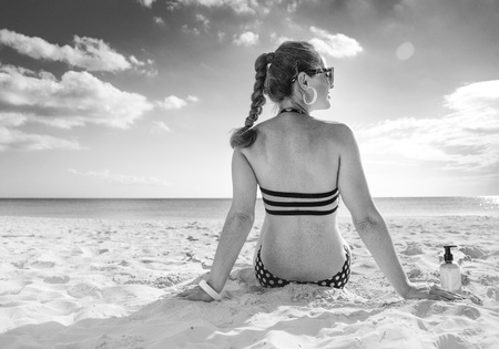 Sun kissed beauty. Seen from behind healthy woman in beachwear on the seashore looking into the distance