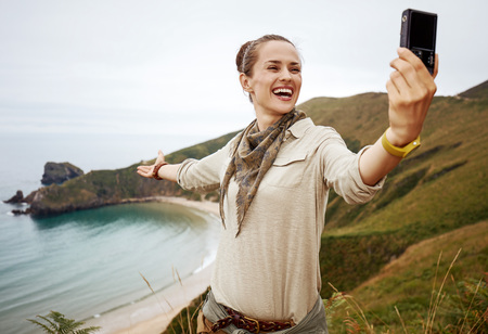 Into the wild in Spain. smiling active woman hiker taking selfie with digital camera in front of ocean view landscape Stock Photo